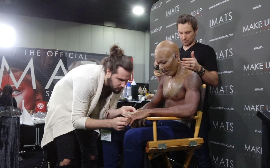 "Matt Silva and Jonah Levy demonstrate ""aging"" make-up on model Dondrey Jackson -- a work in progress, to which a costume was later added. (photo: Mark Gresham)"