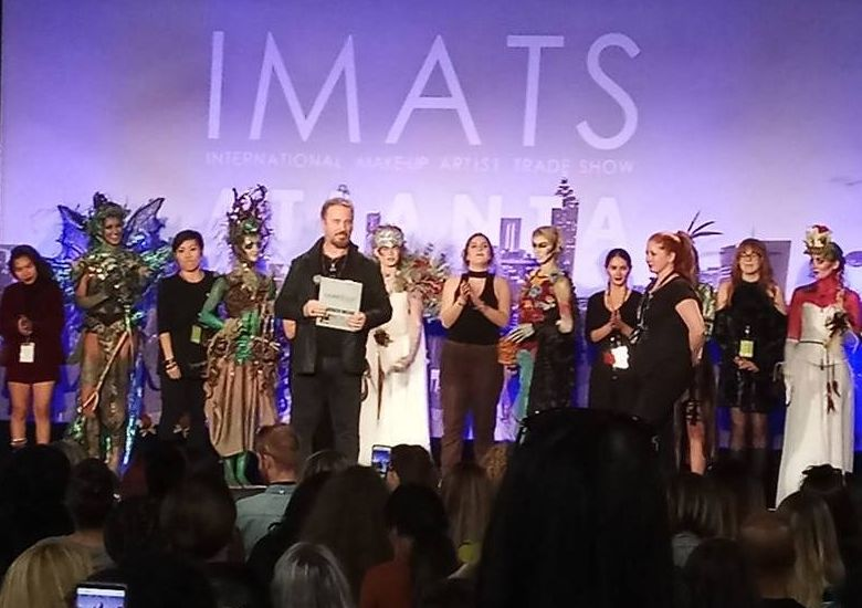 "Surrounded by artists and their design models, IMATS founder Michael Key (fifth from left) presents awards for a ""Battle of the Brushes"" competition."