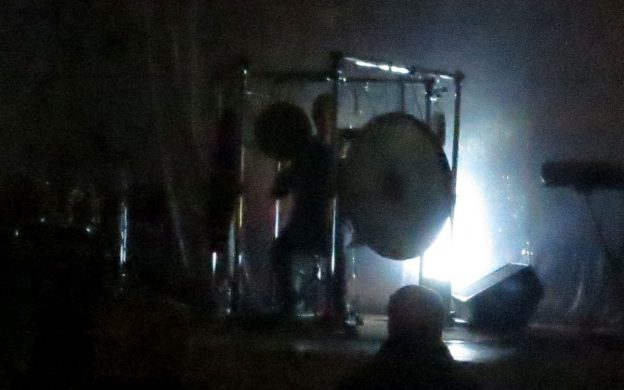 Except for slow strobe lights illuminating from behind, percussionist Jon Mueller's performance was cloaked in darkness.
