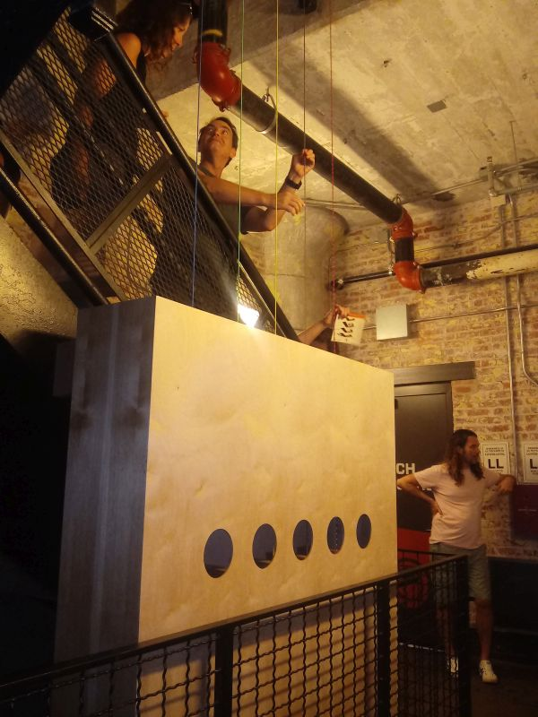 """The wooden sound box at the bottom of the 10 story tall """"Escalier Forte"""" by sculptor Mark Wentzel and sound designer Andrew Lackey, who demonstrates the instrument for an observer. (photo: Mark Gresham)"""