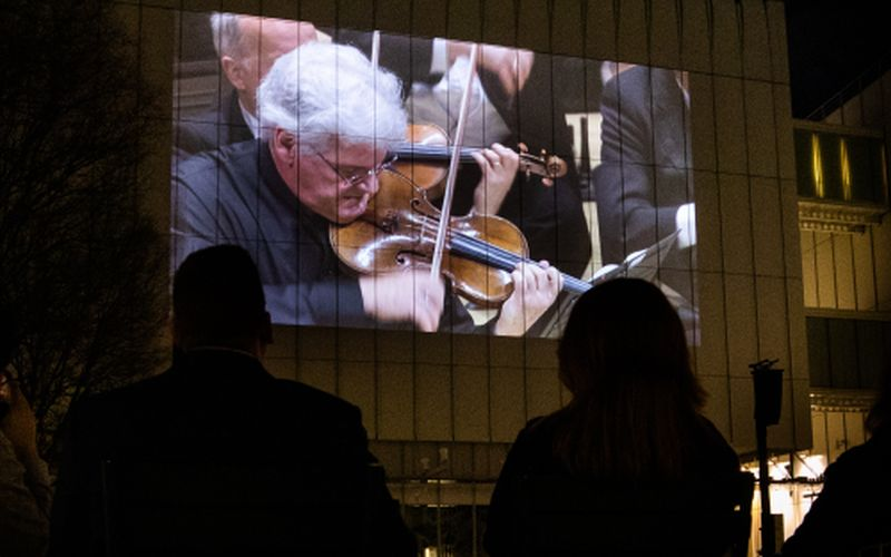 Violinist Pinchas Zukerman projected on the face of the Anne Cox Chambers Building, parts of the live streaming from Wednesday's special concert. (credit: Jeff Roffman)