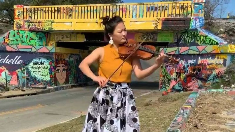 AMP faculty violinist Grace Kim streams from in front of the Graffito Bridge in Pensacole, Florida, from where she teaches virtual lessons. (AMP TV)