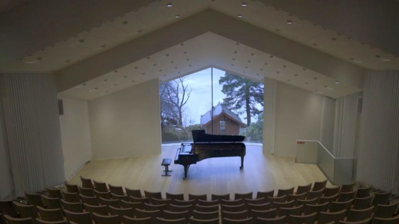The recital hall of the Edvard Grieg Museum. Through the wingow behond the piano can eb sen the cottage that was Grieg's composing studio. )video frame. Spivey Hall/OCL)
