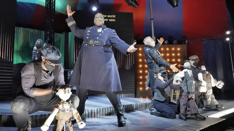 """Joshua Conyers as police chief Jackie """"Tiger"""" Brown, with Macheath and the puppet chorus of thugs. (credit: Ken Howard)"""